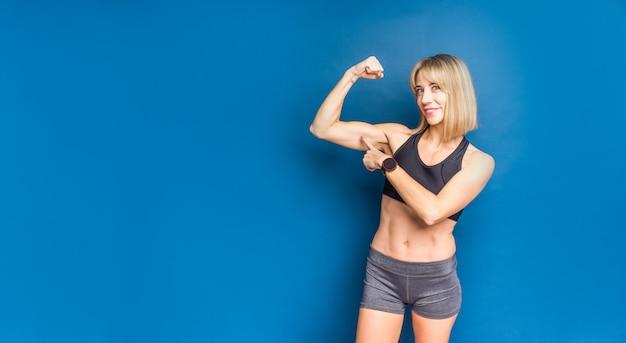 Retrato da bela mulher caucasiana atlética no sutiã esportivo e shorts mostrando o bíceps da mão dela. espaço azul. copie o espaço Foto Premium