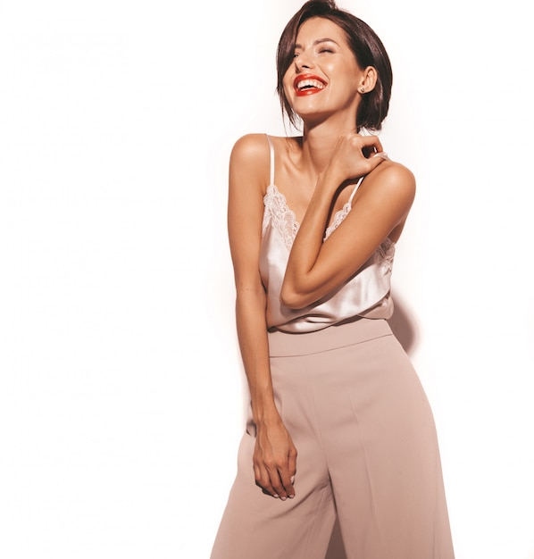 Retrato da bela mulher morena sensual sorridente. garota com roupas clássicas bege elegantes e calças largas. modelo isolado no branco Foto gratuita