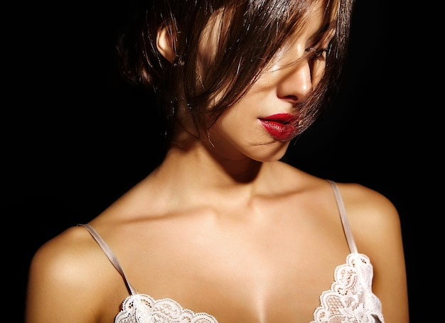 Retrato da bela mulher sexy morena bonita sensual com os lábios vermelhos em lingerie de pijama em fundo preto. com cabelo cobrindo o cabelo Foto gratuita