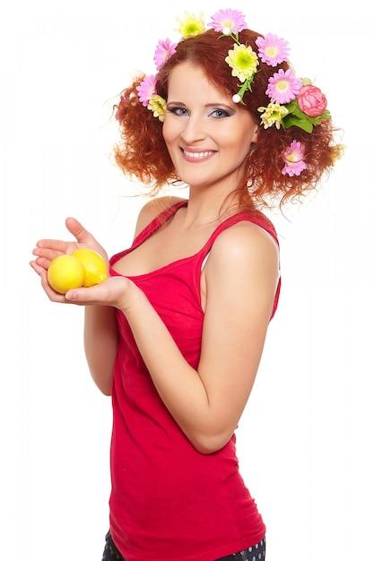 Retrato da bela ruiva sorridente mulher ruiva em pano vermelho com flores coloridas rosa amarelas no cabelo isolado no branco com limão nas mãos Foto gratuita