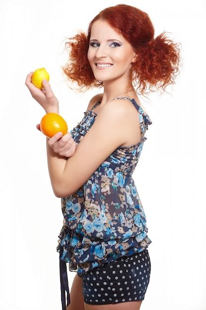 Retrato da bela ruiva sorridente mulher ruiva no verão vestido isolado no branco com laranja e limão Foto gratuita