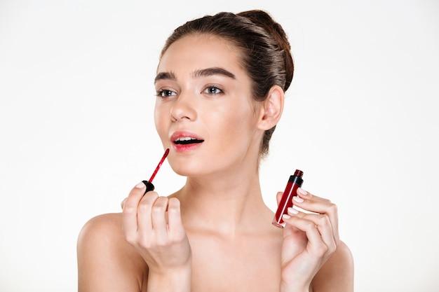 Retrato da beleza da elegante senhora seminua com cabelo no coque, aplicando gloss vermelho, olhando de lado Foto gratuita