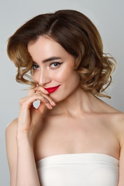 Retrato da beleza da menina bonita com cabelo encaracolado, maquiagem olho de gato, lábios vermelhos Foto Premium