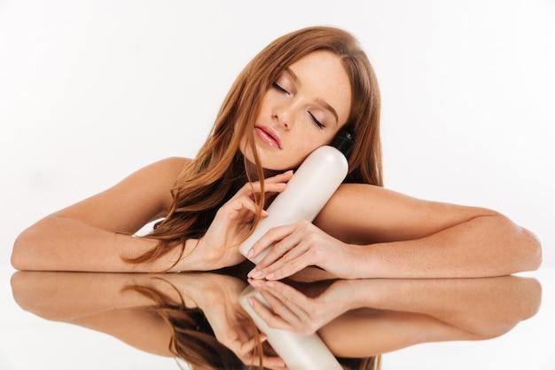 Retrato da beleza da misteriosa mulher ruiva com cabelos longos, sentado junto à mesa de espelho com uma garrafa de loção Foto gratuita
