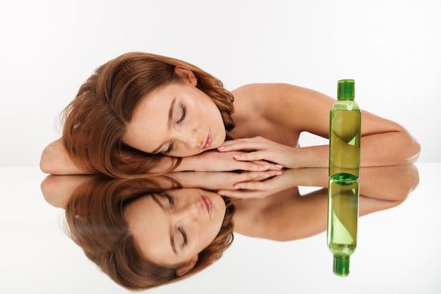 Retrato da beleza da mulher bonita ruiva com cabelos longos, deitado na mesa de espelho com os olhos fechados, perto da garrafa de loção Foto gratuita