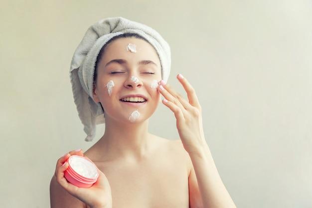 Retrato da beleza da mulher em toalha na cabeça com máscara nutritiva branca ou creme no rosto Foto Premium