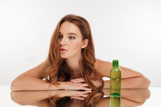 Retrato da beleza da mulher gengibre feminino com cabelos longos reclina na mesa de espelho com uma garrafa de loção Foto gratuita