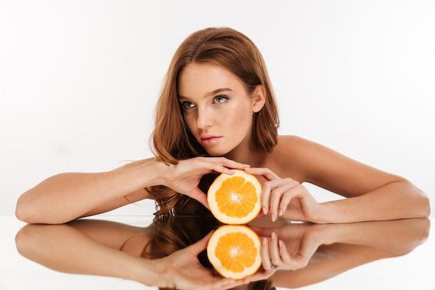 Retrato da beleza da mulher gengibre focada, com cabelos longos, reclina na mesa de espelho, mantendo a laranja e olhando para longe Foto gratuita