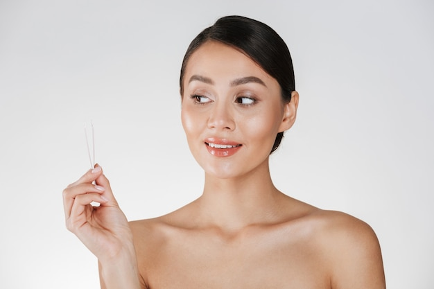 Retrato da beleza da mulher morena atraente sincero olhando pequenas pinças segurando na mão, isolado sobre o branco Foto gratuita