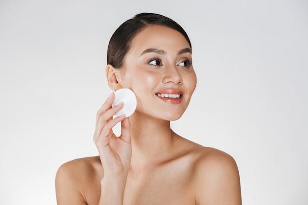 Retrato da beleza da mulher morena sorridente com pele saudável macia, removendo a maquiagem com a almofada de algodão, isolada sobre o branco Foto gratuita