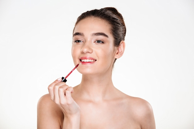 Retrato da beleza da senhora seminua bonita com cabelo em coque aplicando gloss vermelho com sorriso e olhando de lado Foto gratuita