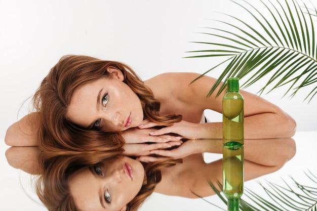 Retrato da beleza de calma mulher ruiva com cabelos longos, deitado na mesa de espelho com uma garrafa de loção enquanto olha Foto gratuita