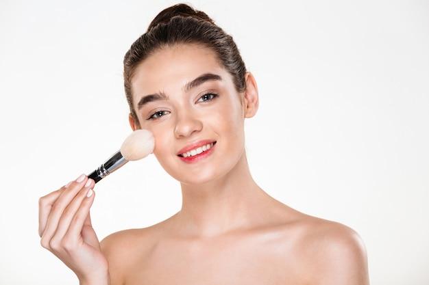 Retrato da beleza de mulher seminua sorridente com pele fresca, aplicar maquiagem com pincel macio e olhando Foto gratuita