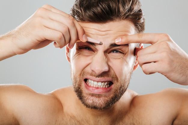 Retrato da beleza de um jovem, arrancar as sobrancelhas com pinça Foto gratuita