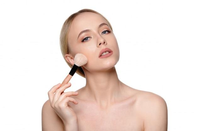 Retrato da beleza de uma bela mulher seminua sorridente posando com pincéis de maquiagem Foto Premium