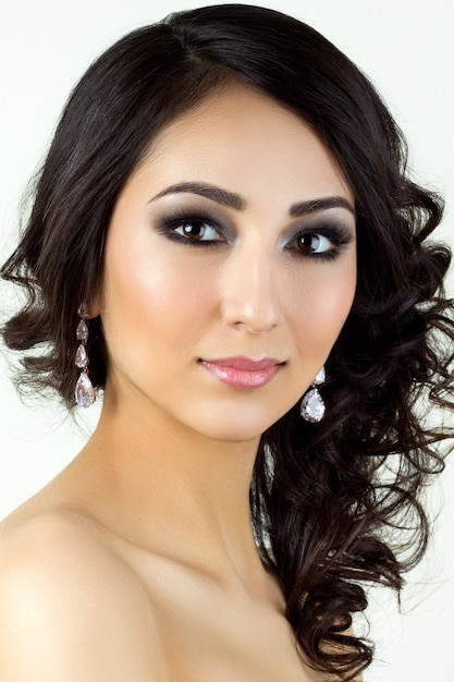 Retrato da beleza de uma jovem morena com brincos Foto Premium