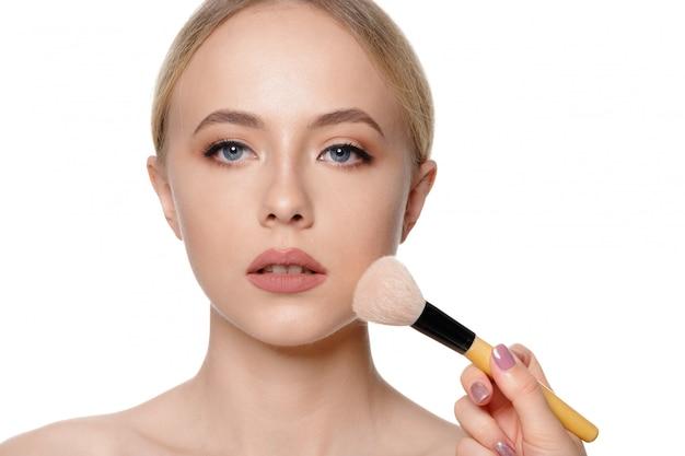 Retrato da beleza de uma mulher bonita meio nu sorridente posando com pincéis de maquiagem Foto Premium