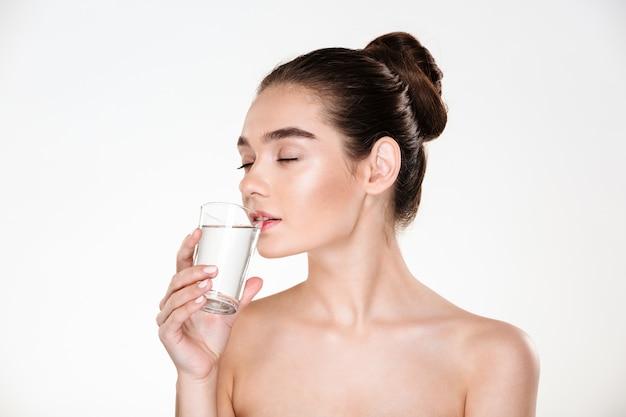 Retrato da beleza de uma mulher muito feminina com pele macia, bebendo água fresca e fresca de vidro transparente com os olhos fechados Foto gratuita
