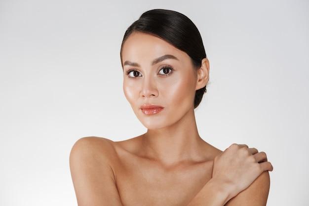 Retrato da beleza de uma mulher seminua olhando na câmera e tocando seu ombro gentil, isolado sobre o branco Foto gratuita