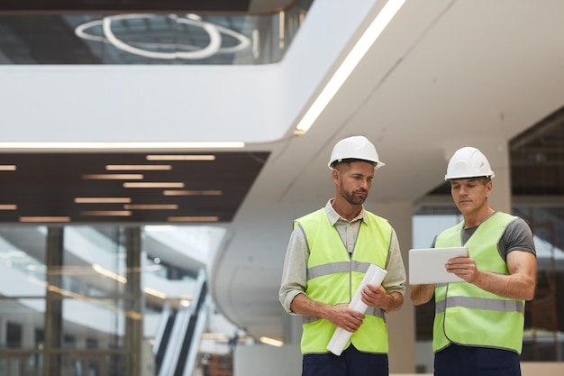 Retrato da cintura para cima de dois empreiteiros de construção maduros usando tablet digital em um prédio de escritórios no canteiro de obras, Foto Premium
