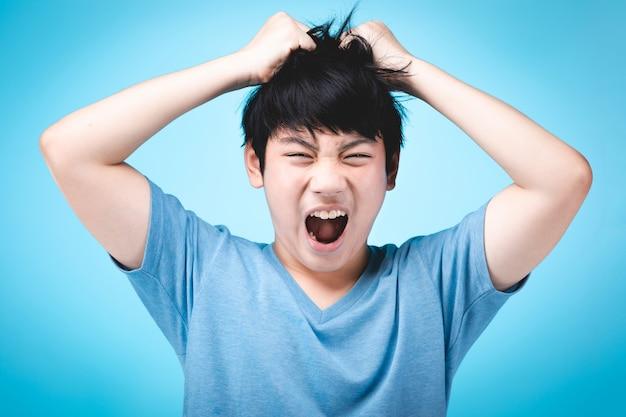 Retrato da criança asiática irritada no azul. Foto Premium