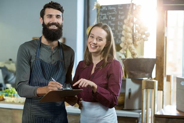 Retrato da equipe de padaria sorridente escrevendo na área de transferência no balcão Foto Premium