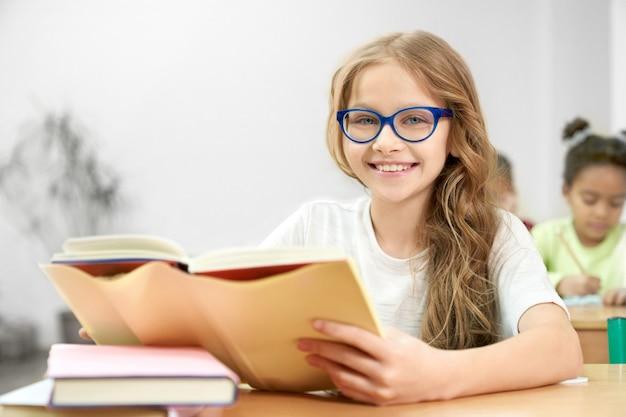 Retrato da estudante nova em vidros azuis com o livro aberto na sala de aula. Foto Premium