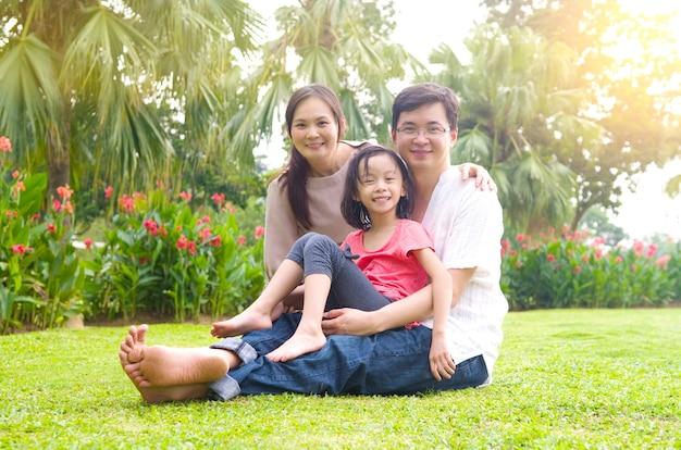 Retrato da família asiática feliz alegre no parque ao ar livre durante o por do sol do verão. Foto Premium