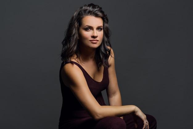 Retrato da jovem mulher no fundo cinzento. Foto Premium