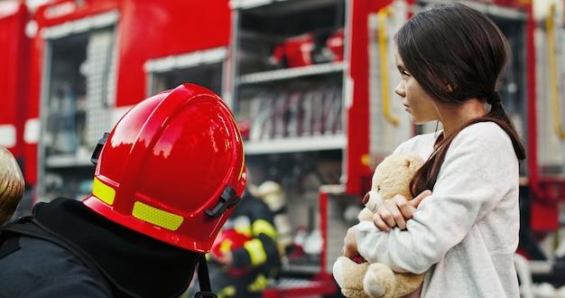 Retrato da menina asiática pequena resgatada com o homem do sapador-bombeiro que está o caminhão de bombeiros próximo. bombeiro em operação de combate a incêndio Foto Premium