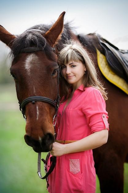 Retrato da menina bonita com um cavalo castanho no parque Foto Premium