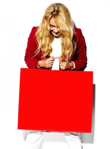 Retrato da menina bonito feliz doce surpresa mulher loira bonita segurando nas mãos grande sacola de compras em roupas hipster vermelho isolado no branco Foto gratuita