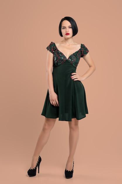 Retrato da menina bonito no vestido curto e em sapatos de salto alto posando com a mão na cintura no estúdio Foto Premium