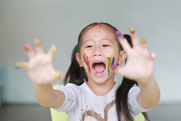 Retrato da menina de sorriso que olha através de seus mãos e mordente coloridos pintados na sala das crianças. Foto Premium