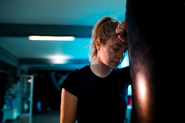 Retrato da menina do pugilista cansado após o treinamento com o saco de perfuração pesado no gym. Foto Premium