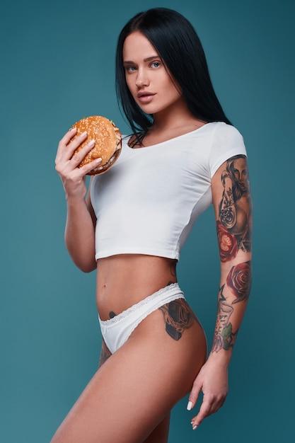 Retrato da menina encantadora tatuagem bonita segurando o hambúrguer Foto Premium