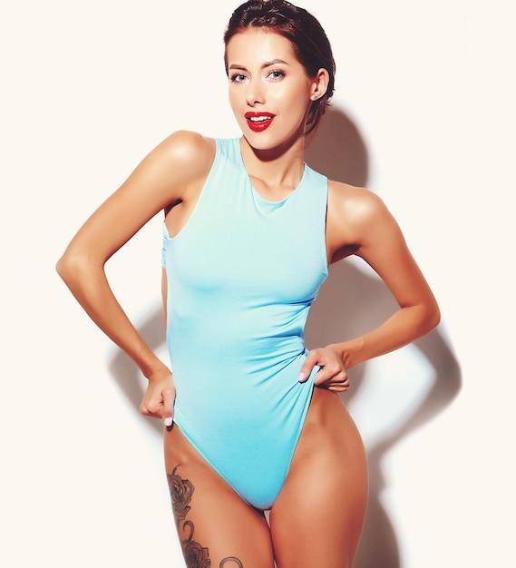 Retrato da menina má bonita mulher morena sexy quente em lingerie de corpo casual verão azul sobre fundo branco Foto gratuita