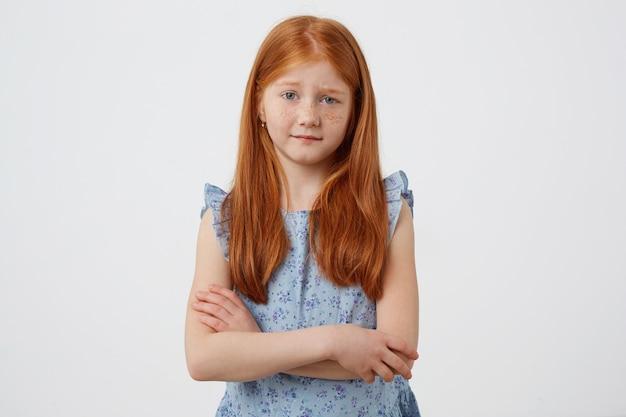 Retrato da menina ruiva de sardas infelizes com duas caudas, descontente olha para a câmera, usa um vestido azul, fica com os braços cruzados sobre fundo branco. Foto gratuita