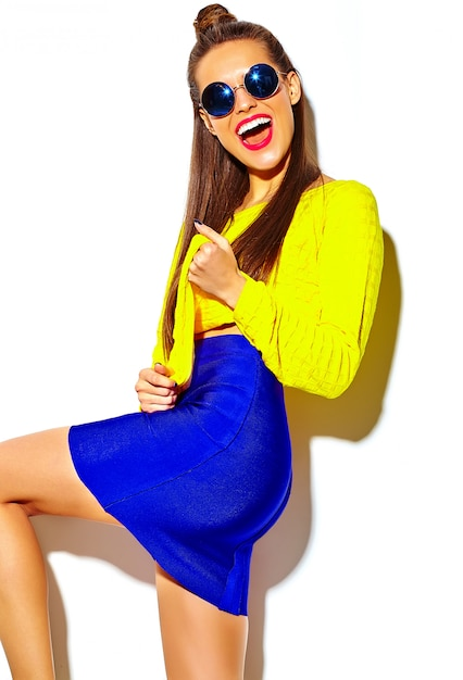 Retrato da moda alegre, sorrindo garota hippie enlouquecendo em roupas de verão amarelo colorido casual com lábios vermelhos isolados no branco Foto gratuita