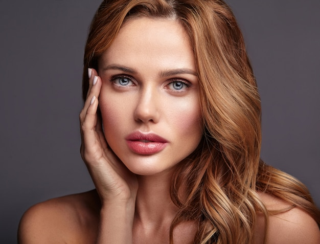 Retrato da moda beleza de modelo jovem loira com maquiagem natural e pele perfeita posando. tocando seu rosto Foto gratuita