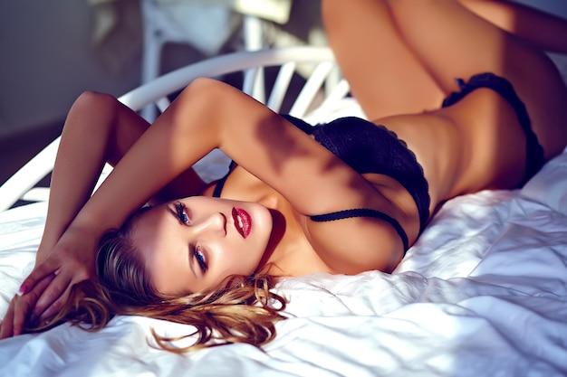 Retrato da moda da bela jovem sexy vestindo lingerie preta na cama Foto gratuita