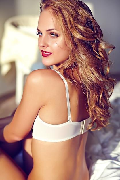 Retrato da moda da bela modelo adulto jovem loira sexy vestindo lingerie erótica branca posando na luz interior no nascer do sol da manhã Foto gratuita