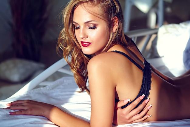 Retrato da moda da bela modelo adulto jovem loira sexy vestindo lingerie erótica preta, deitada na cama ao pôr do sol Foto gratuita