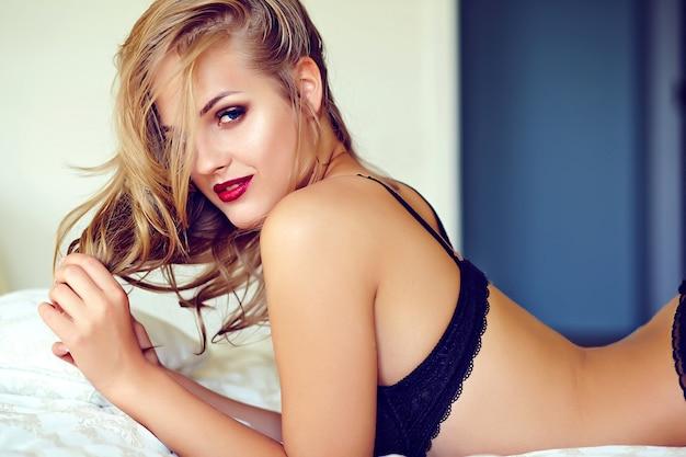 Retrato da moda da bela modelo adulto jovem loira sexy vestindo lingerie erótica preta posando no interior luz da manhã Foto gratuita