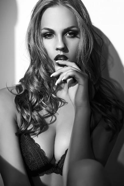 Retrato da moda da bela modelo adulto jovem loira sexy vestindo lingerie erótica preta posando perto de parede cinza Foto gratuita
