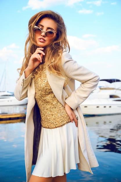 Retrato da moda da bela modelo com cabelos crespos da moda ombre, casaco de lã creme de outono aconchegante, top dourado e óculos de sol, incrível whew no porto de temor e iate clube. Foto gratuita