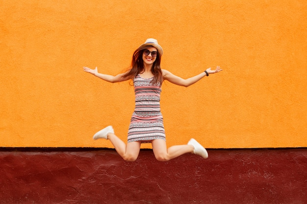 Retrato da moda da mulher muito sorridente em óculos de sol e chapéu de salto Foto Premium