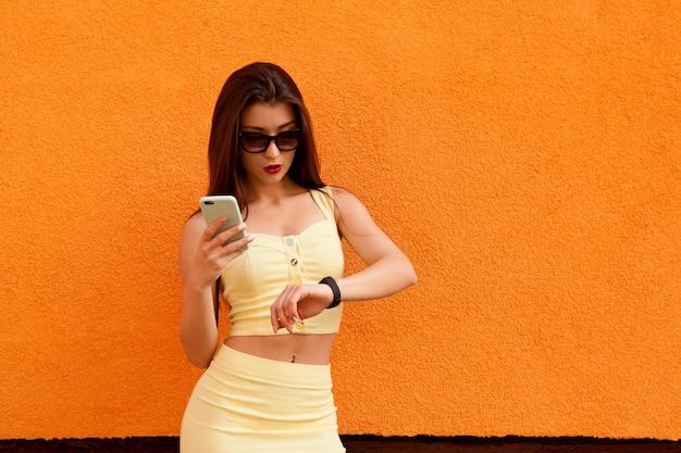 Retrato da moda da mulher muito sorridente em óculos de sol em pé com o smartphone Foto Premium