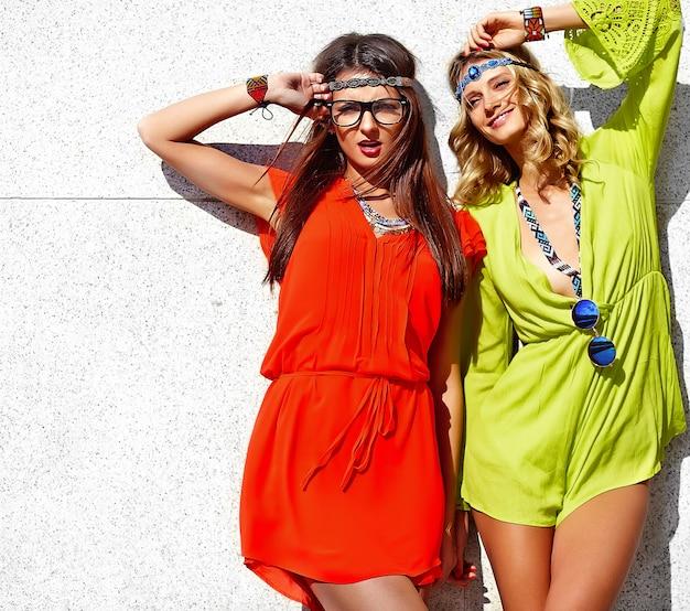 Retrato da moda de dois modelos de mulheres jovens hippie em dia ensolarado de verão em roupas brilhantes coloridas hipster Foto gratuita