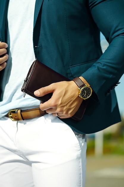 Retrato da moda do homem jovem bonito modelo de empresário em pano casual terno com acessórios nas mãos Foto gratuita